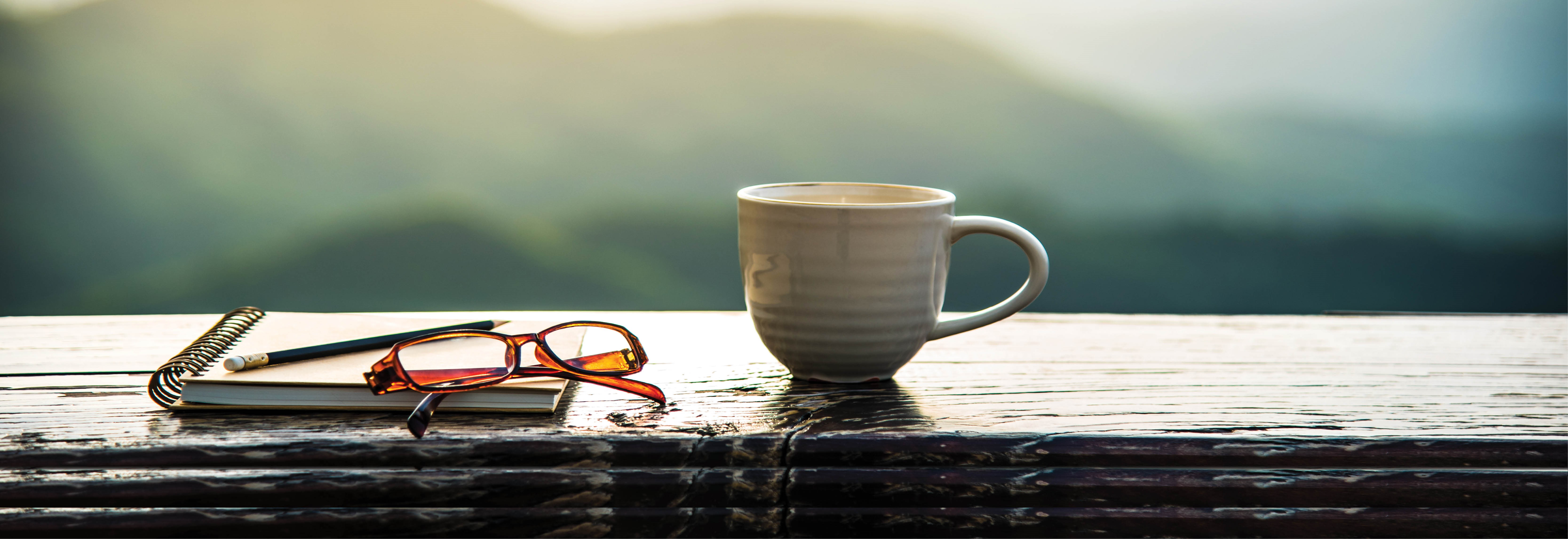 coffee mug, note pad and glasses on porch railing