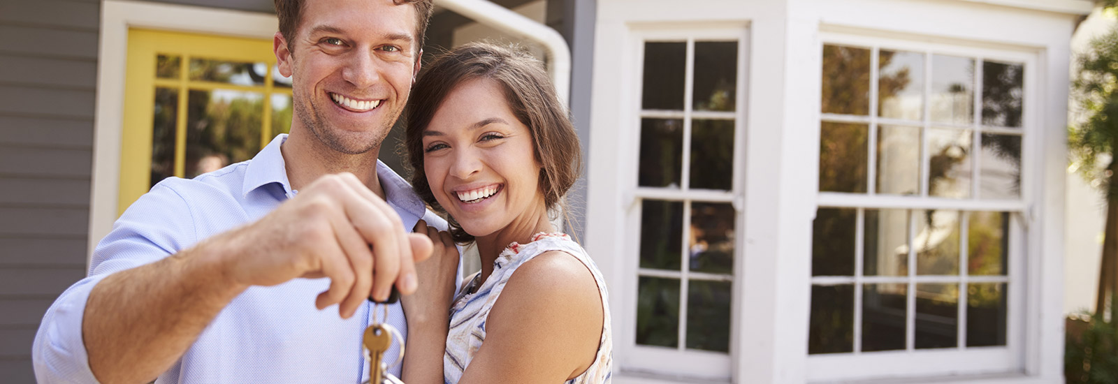 Young couple with keys to new house