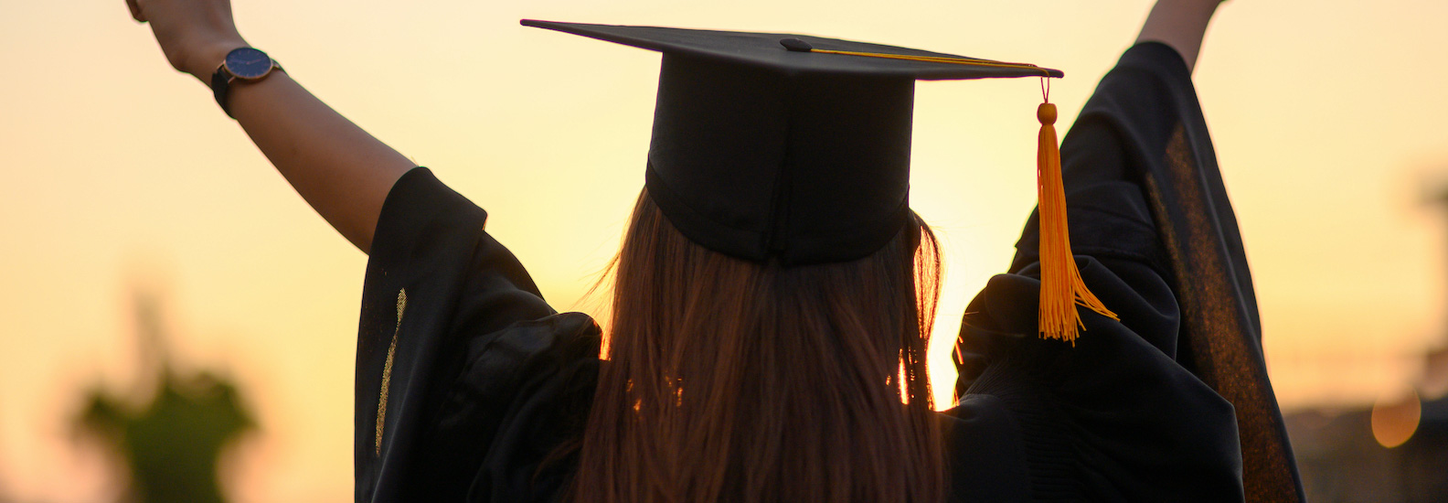 woman wearing black graduation hat and gown with arms up celebrating